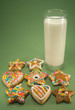 Christmas cookies and a glass of milk isolated on green paper
