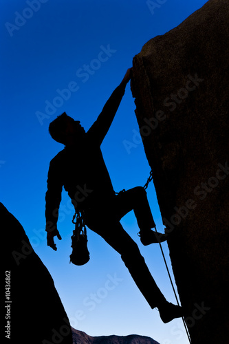 Climber clinging to  an overhanging rock face.