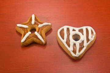 Decorated star and heart cookies on red background