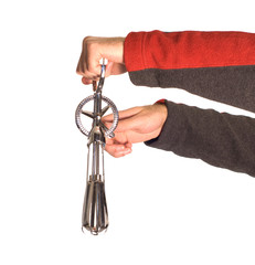 An oldfashioned egg beater, being held by someone