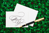 Thank you card and pen on leaf and holly berry background