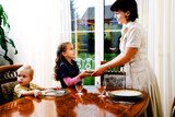 daughter and mom setting the table for a meal poster