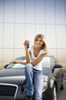 Young woman holding keys to new car.