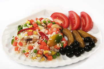 Risotto on a plate with tomatoes, olives and cucumbers