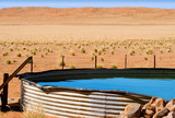 corrugated iron dam with cool blue water on desert farm poster