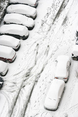 elevated view of parked cars covered with snow in winter time