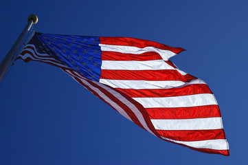 Backlit american flag blowing in the wind against blue skies