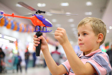 Boy in shop with toy helicopter