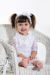 Little Girl Sitting in a rotton armchair laughing
