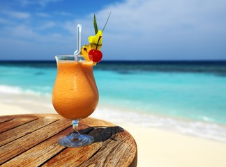 Bocal of fruity cocktail on a beach table