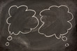 two blank speech bubbles or callouts sketched on blackboard