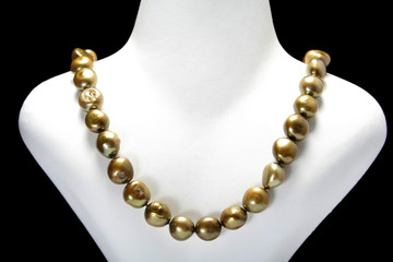 A gold coloured bead necklace.