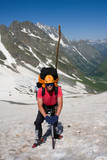 Backpacker with ice-axe in high mountains poster