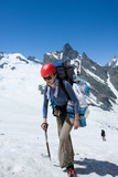 Backpacker girl with ice-axe in high mountains poster