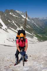 Backpacker with ice-axe in high mountains