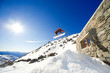 Snowboarder jumps off cabin roof with blue sky background