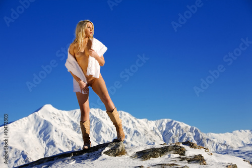 Young woman poses naked on top of a snow covered mountain