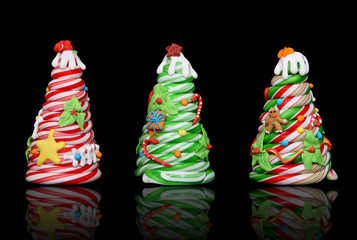 Three colorful candy cane Christmas trees over black background