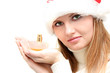 Beautiful girl in santa hat  holding bottle of perfume