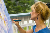 A female artist painting on canvas on her studio balcony poster