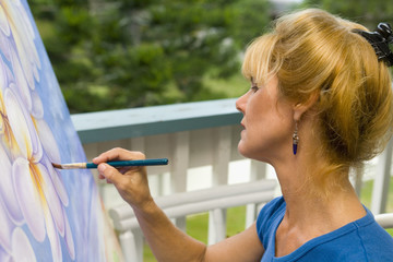 A female artist painting on canvas on her studio balcony