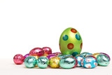speckled easter egg surrounded by foil wrapped eggs. poster