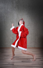Happy dancing woman in the red costume of Santa Claus
