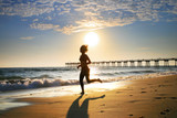 Fototapety Woman at the beach running by the ocean at sunset
