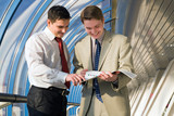 Two young businessmen discuss results of work poster