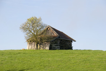 Holzhütte auf einer Anhöhe.