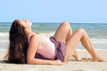 The beauty young woman lies on sand at sea coast