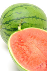 Close up of fresh watermelon halved over white