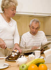 Elderly couple look a book during breakfast