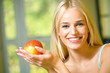 Portrait of young happy smiling woman with apple