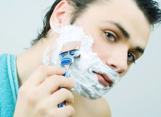 Young man shaving his beard.