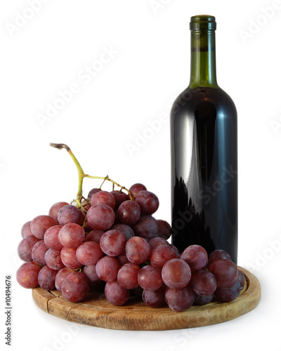bottle of red wine and a bunch of red grapes on white background