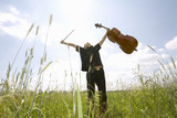 Young man standing in field with cello, low angle view