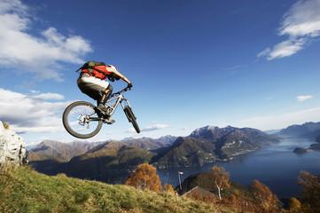 Italien, Comer See, Mountainbiker springt mit seinem Rad