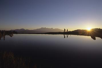 Österreichischen Alpen, zwei Personen zu Fuß in der Nähe eines Ufers