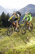 Austria, Tirol, young couple riding bicycles on mountain