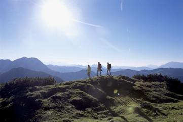 Österreich, Salzburger Land, drei Menschen wandern in den Alpen