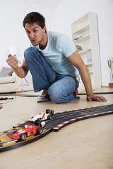 Vater und Sohn spielen mit Spielzeugauto Carrerabahn