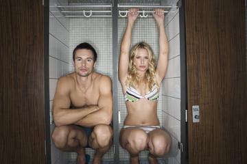 Paar sitzt im Schrank eines Umkleideraums im Schwimmbad