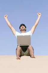 Mann sitzen auf Sand mit Laptop
