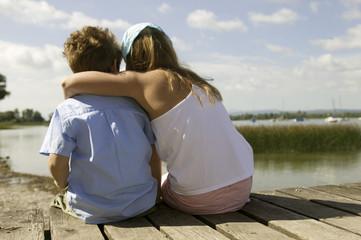 Mädchen und Junge sitzen auf Steg, Rückansicht