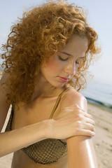 Frau jung Sonnencreme auftragen auf Strand, close-up