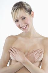 Junge nackte Frau verdeckt die Brüste