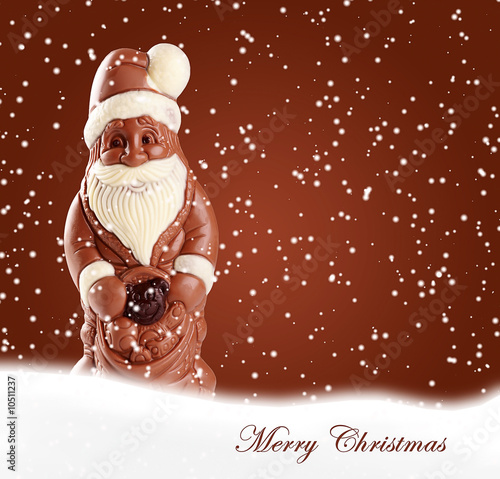 Chocolate figures of Santa in winter background