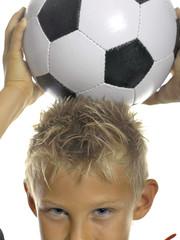 Junge, Kind mit Fußball auf Kopf