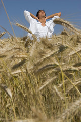 Junger Mann steht im Getreidefeld